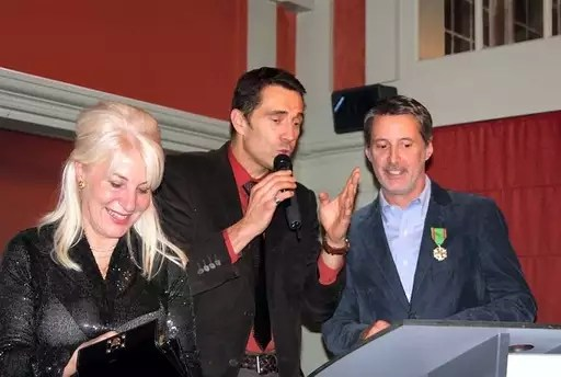 Antoine de Caunes tout sourire aux côtés de son ami, Olivier Linot et de Nicole Ameline députée, qui lui a remis l'insigne.