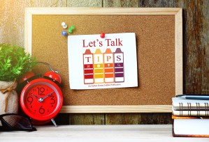 Let's Talk Tips Newsletter graphic. A photo shows a close up of a cork board hanging on a wall above a desk. On the desk to the left of the cork board is a plant and a red double bell alarm clock. To the right of the cork board is a hardcover book with a spiral notebook and pen on top of it. Pinned to the very center of the cork board by a single red pin is the Let's Talk Tips logo printed on a single piece of white paper. The logo itself consists of 4 multicolored crayons standing side by side. Each crayon has a different letter at the top of it, together spelling out the word, TIPS.