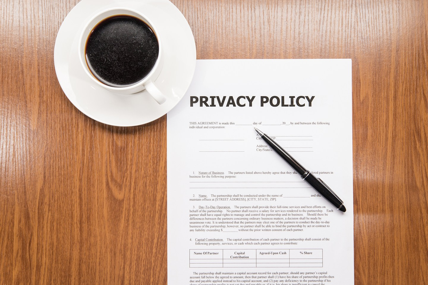 A paper Privacy Policy document sits on a wooden desk with a pen on top of it. Just above the sheet of paper is a cup of coffee.
