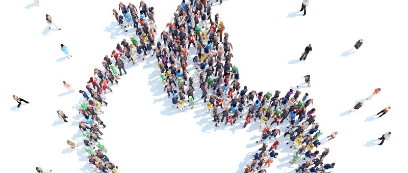 Aerial photograph looking down on a large group of people that have come together to form the International Symbol of Access (ISA), also known as the (International) Wheelchair Symbol, which consists of a stylized image of a person in a wheelchair.