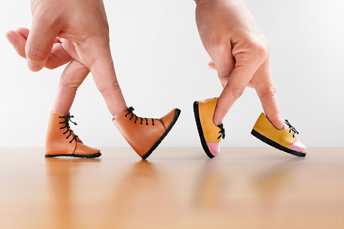 Two hands, one with miniature boots on its fingers and the other with miniature loafers on its fingers walk together across a table.