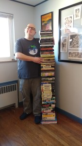 The author, next to a nose-high stack of one copy of everything he's published
