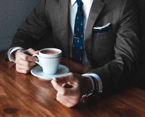 Mann im Anzug trinkt Kaffee