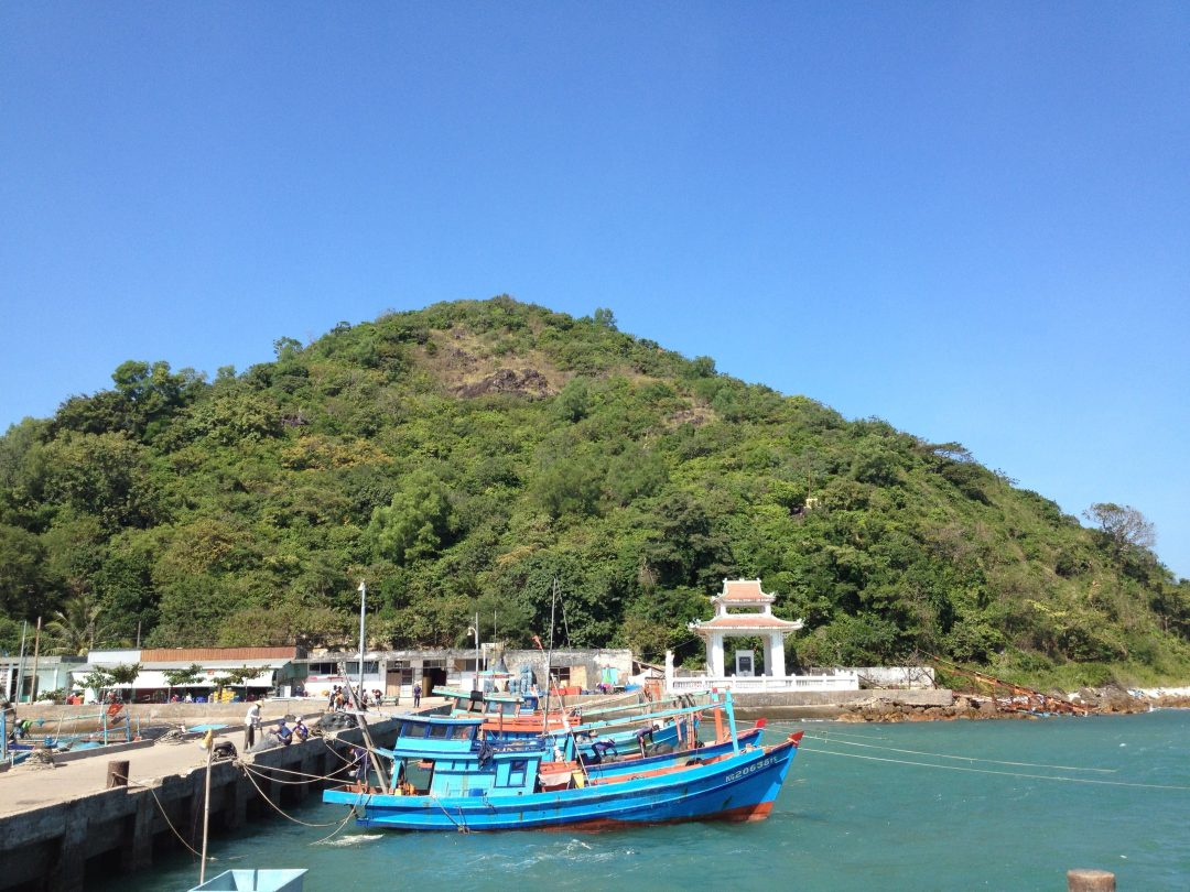 A boat docked in front of a hill.