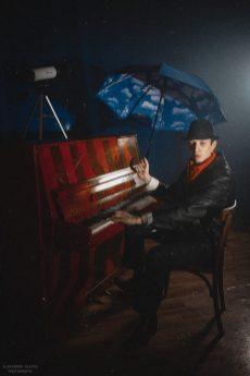Мужчина с зонтом у пианино