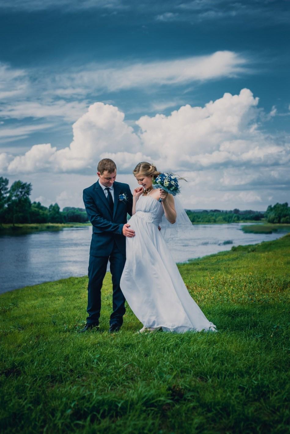 Жених и беременная невеста на берегу реки