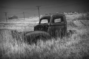 old-truck-abandoned-in-the-grass-in-infrared-black-and-white-at-the-ghost-town-by-okaton-south-dakot-randall-nyhof