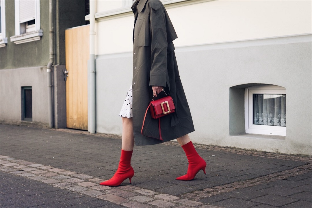 red boots and Boyy it bag styled with a trench