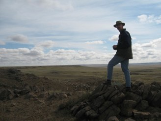 PHOTO: Pat Herendeen poses on the vast steppe, binoculars in hand.