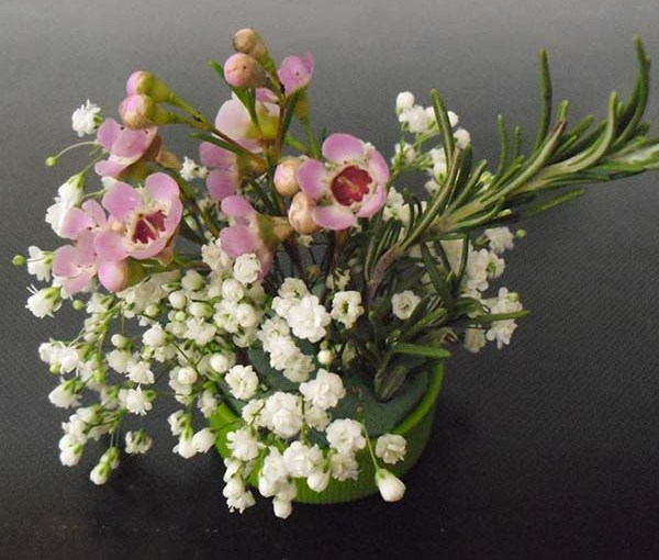 PHOTO: A bottlecap posey of waxflower, a sprig of rosemary, and baby's breath.