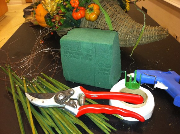 Essential tools include pruners, floral foam, and a hot glue gun.