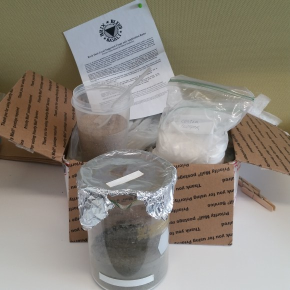 PHOTO: a box of basalt, a cup of sand, a bag of feldspar, and a glass beaker containing the Martian soil mixture