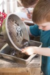 PHOTO: A young boy mixes mud in kitchen baking pans.