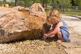 PHOTO: A young visitor discovers the boulder bubbler at the Nature Play Garden.