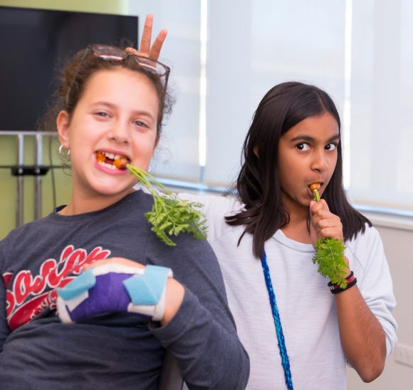PHOTO: Two girls are eating carrots. One holds two fingers up behind the other's head to give her bunny ears.