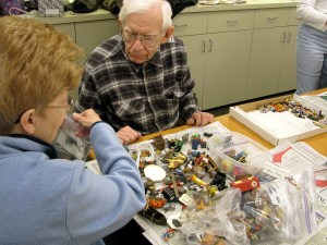 PHOTO: George and Judy Knuth sorting a pile of miniatures.