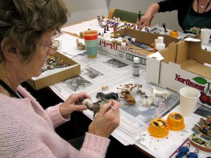 PHOTO: Volunteer painting a horse miniature.