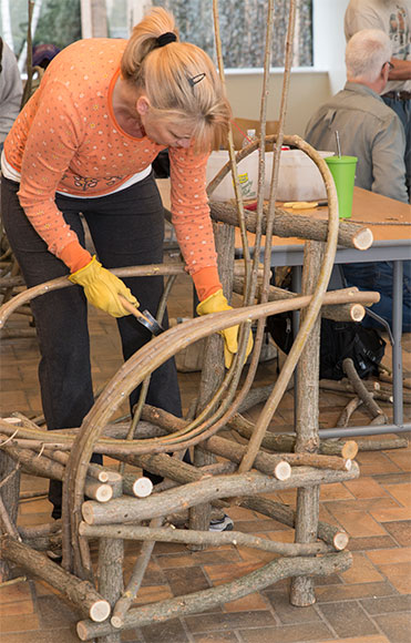 A chair workshop participant begins to attach the bent willow forming the seat and back to her chair frame.