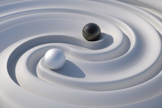 Artistic interpretation of the yin/yang symbol with black and white balls on a fluid white surface