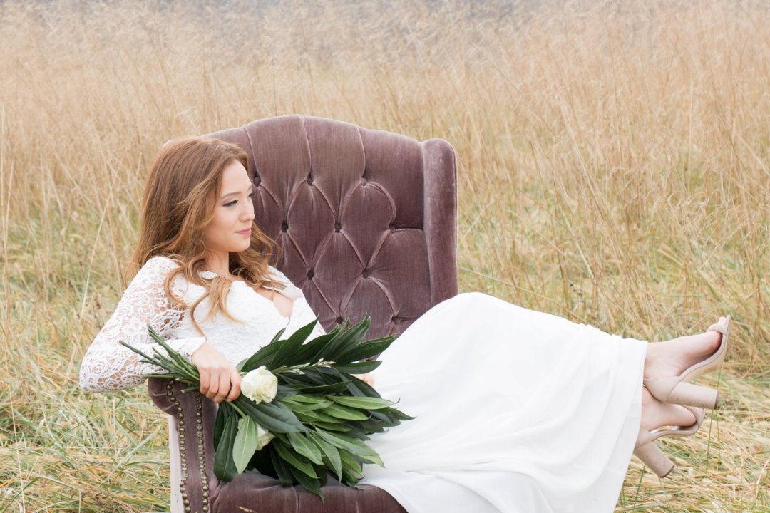 Bride sitting in amethyst-colored vintage wingback chair