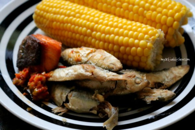 baked salmon and fried smelt fish on a plate with two sweetcorn on hub