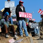 Unemployed men display placards at the road side seeking jobs