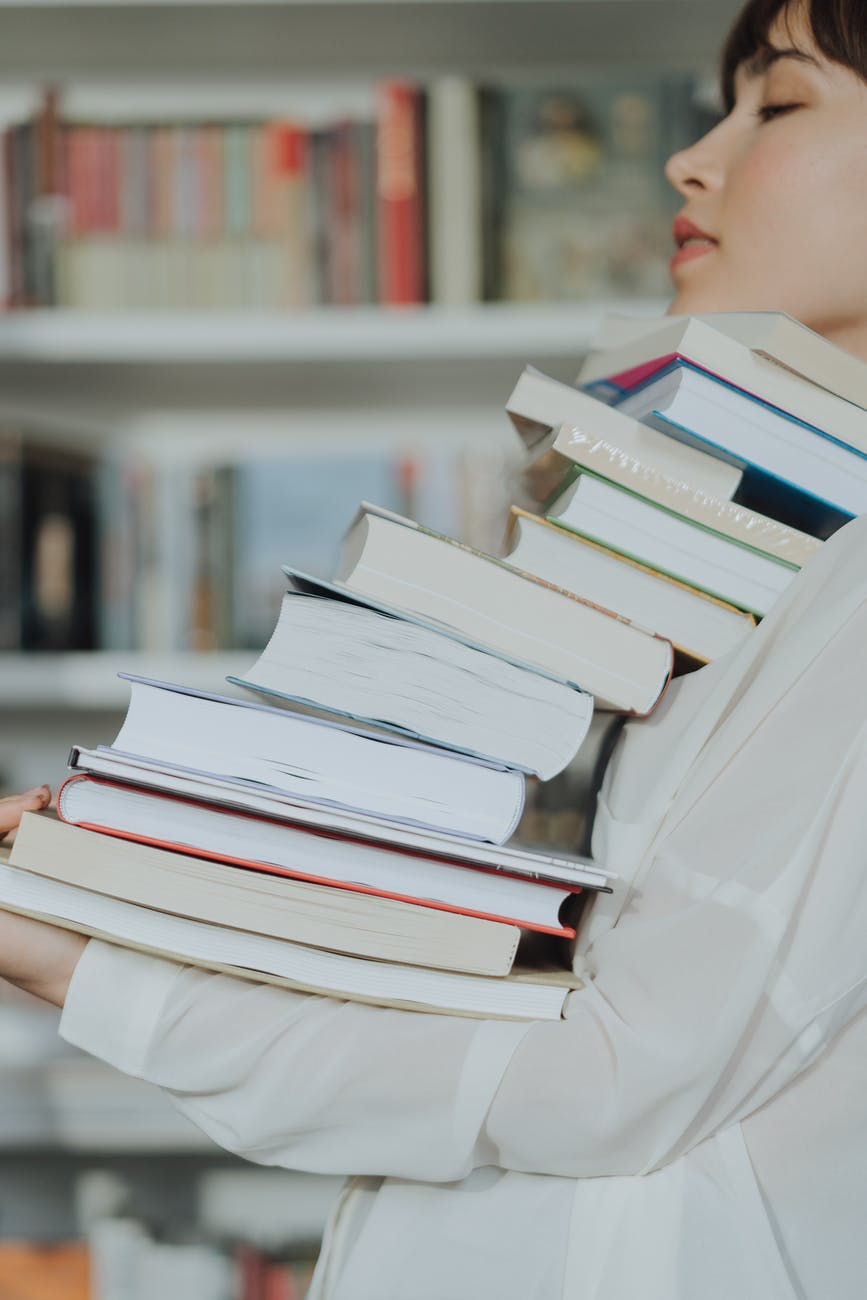 person reading book on book shelf