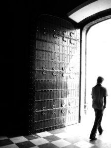 Man Walking Through Large Door