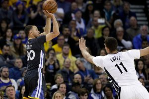 Stephen Curry shooting over Brooklyn's Brook Lopez during the Warriors' win on Saturday. Credit Marcio Jose Sanchez/Associated Press
