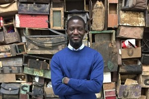 Ibrahim Mahama in front of an installation made from the wooden boxes used by shoe repairmen in Ghana to hold their tools. The work is now on view at White Cube