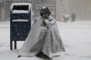 A homeless man asks for money during blizzard-like conditions Feb. 9 in in Boston (CNS photo/Brian Snyder, Reuters).