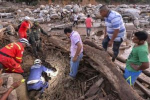 Rescue workers searched among the rubble and fallen trees