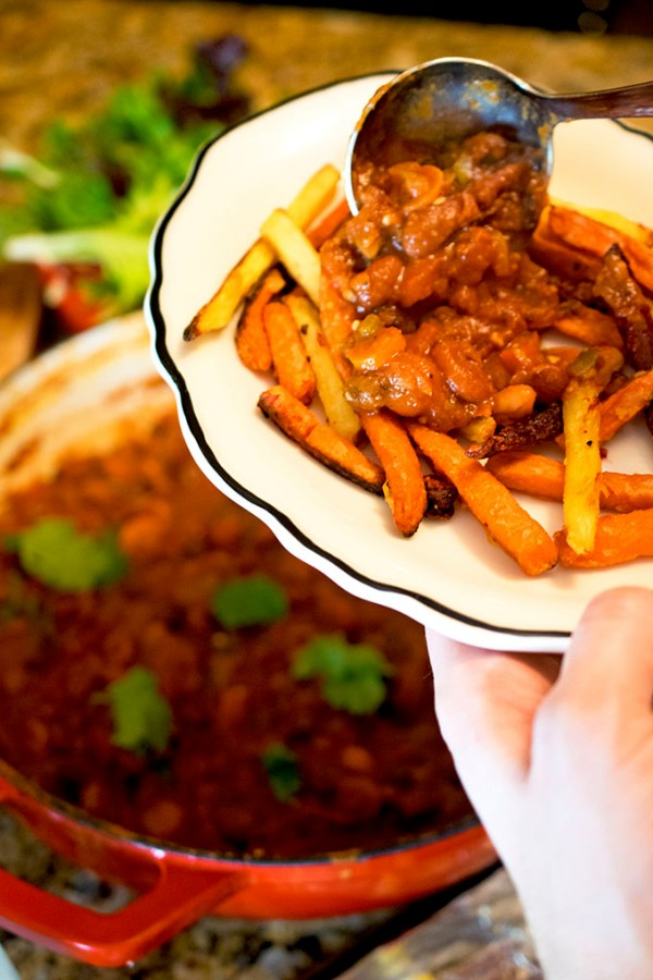 Serving vegetarian chili over roasted root fries.