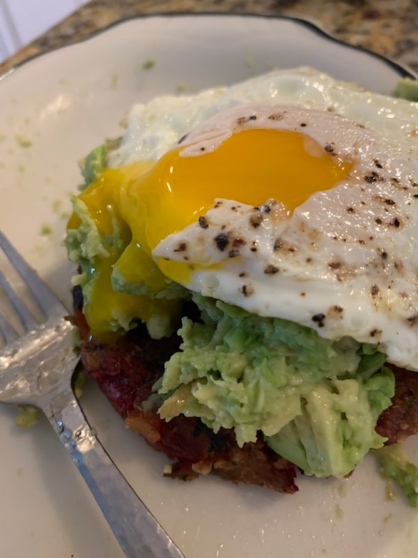 Egg on top of crushed avocado and an Aldi vegetable burger.
