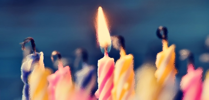46738394 - closeup of some unlit candles and just a lit candle after blowing out the cake