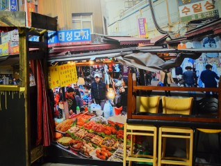 You be the judge of whether a restaurant that insists it's not a traditional Korean from Korea restaurant might be sending mixed messages by putting a wall-sized print of a Korean street market scene outside the restaurant.