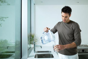 man pouring water from a water purifying pitcher into a glass