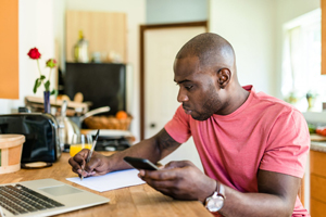 Young athletic black man in red shirt sits at his kitchen table planning his monthly budget