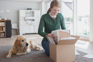 Young white woman carefully packs up an item she sold on eBay in her living room while her faithful Golden Retriever looks on curiously.