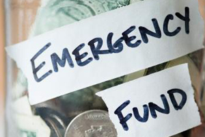 """Close up of the side of a glass jar of money containg bills and coins and labeled """"Emergency Fund"""""""