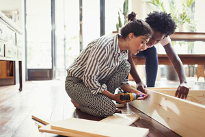 Young bi-racial couple assembles assemble it yourself furniture in their modern home.