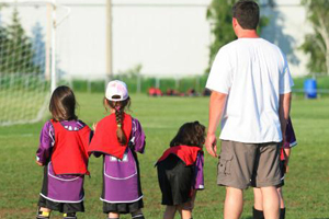 man standing with three young kids on a soccer field sideline