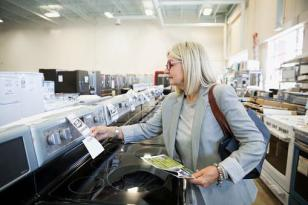 Middle-aged woman in business attire shopping for a new stove in a big-box appliance store.