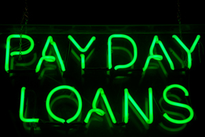 "glowing green neon sign over black background that spells out ""pay day loans"""