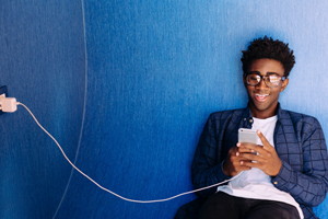 Young black male teen enjoys content on his phone that is plugged into a wall charger.