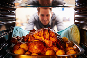 View from inside of oven - young man removes perfectly baked turkey from oven.