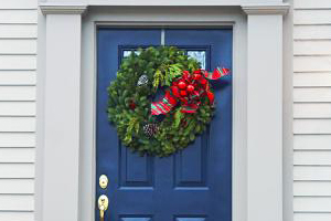 Close-up of the front of a Colonial style house with a navy blue front door decorated with holiday wreath.
