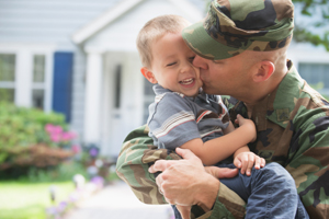 Army soldier holding and kissing his laughing son on the cheek.