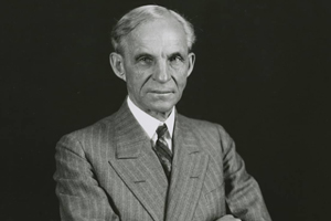 Black and white vintage photo of Henry Ford in business suit facing the camera with arms crossed.
