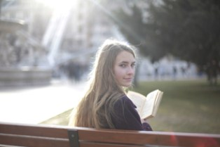 College age girl on bench reading book at school